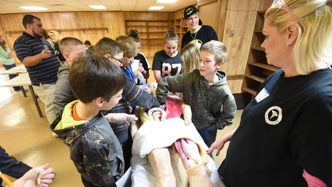 """Mortuary science students from Arkansas State University Mountain Home look as Pinkston Middle School students dig into the chest cavity of  a simulated cadaver named """"Morticia""""  at the Baxter County Fairgrounds on Wednesday, Feb. 24, 2016 during the annual CSI Project. The event has several stations students rotate through to learn various aspects of science through aspects criminal investigation."""