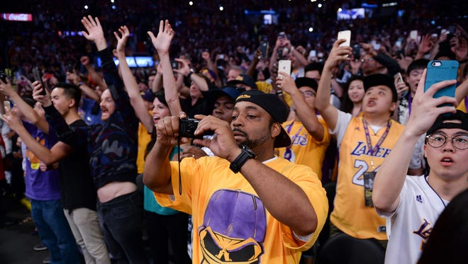 Los Angeles Laker fans celebrate and shoot snapshots as time runs out in the Lakers' win over the Utah Jazz in Kobe Bryant's final game of his NBA career at Staples Center.