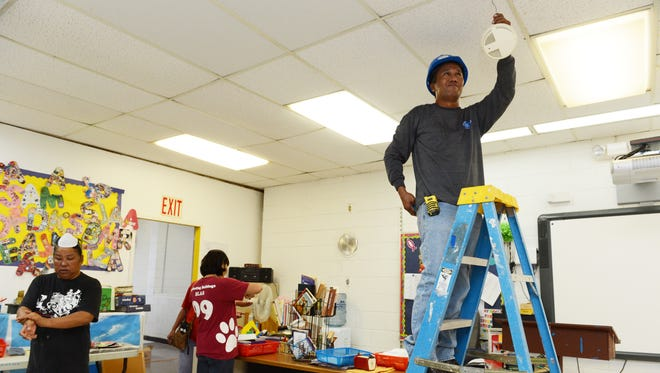 In this November 2013 file photo, Fronie Ingaran, right, of Orion Construction Corp., removes an old fire alarm in a Simon Sanchez High School classroom as school aides clean the room.