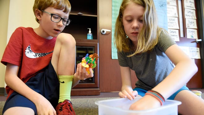 Campers manipulate small toys at the ADHD Summer Treatment Program at Currey Ingram Academy. These activities can help children with their fine motor skills.