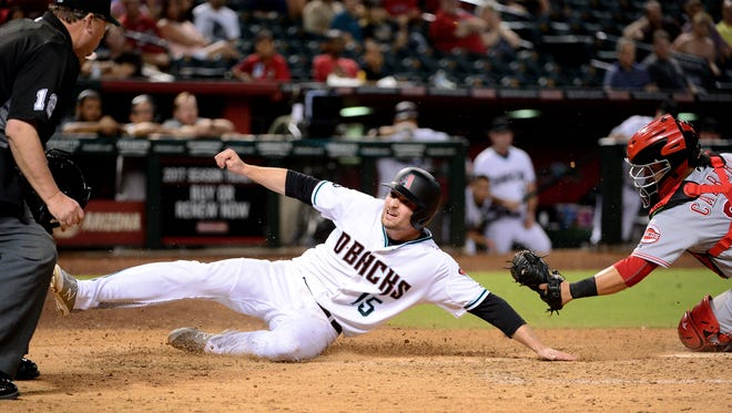Phil Gosselin #15 of the Arizona Diamondbacks safely slides by Ramon Cabrera #37 of the Cincinnati Reds to score in the tenth inning at Chase Field on August 26, 2016 in Phoenix, Arizona.