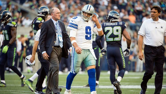 Dallas Cowboys quarterback Tony Romo (9) walks off the field after getting injured during the first quarter during a preseason game against the Seattle Seahawks at CenturyLink Field.