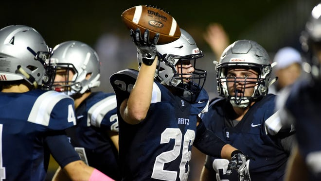 Noah Jones of Reitz raises the football after coming up with the Central fumble during the first quarter of the game at the Reitz Bowl in Evansville Friday.