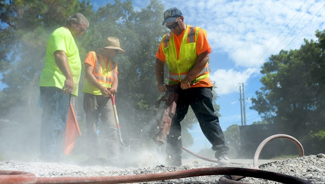 John Sales (right) runs a jackhammer to break up concrete around a manhole cover Aug. 3, 2016, as Arnie Zonfrilli (left) and Peter Gent watch for traffic along a stretch of 21st Street to be repaved from Georgia Avenue to Virginia Avenue in Fort Pierce.
