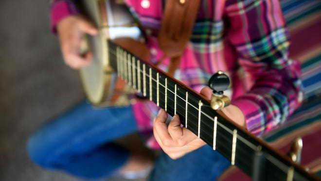 Uma Peters, 9, plays her banjo at her home Tuesday, Nov. 1, 2016, in Nashville.