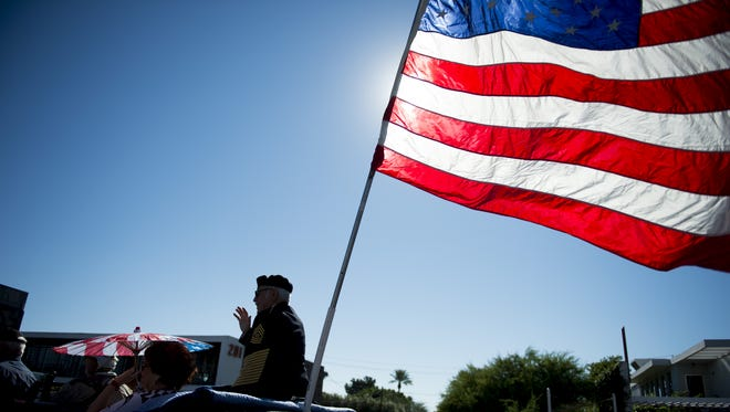 Military vehicles transport service members down Camelback Road during the Veterans Day Parade in central Phoenix on Nov. 11, 2016.