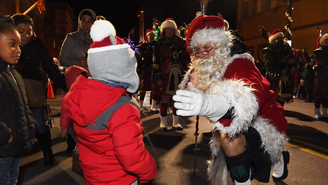 Jaiden Laing, 3, of the Town of Poughkeepsie, goes in for a hug with Santa Claus during the 2016 Celebration of Lights Parade on Main Street in the City of Poughkeepsie.