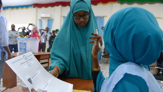 This photo taken on Nov. 16, 2016, shows a Somali poll worker, right,  explaining the voting procedure to a voter before she casts her ballot in Baidoa.