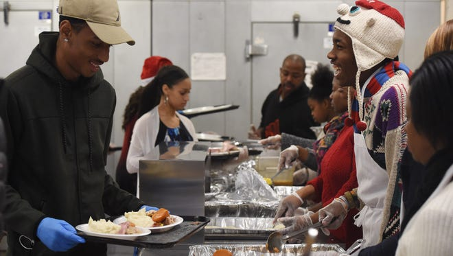 Volunteers laugh while serving food at the annual Eileen Hickey Holiday Dinner at the Lunchbox in the City of Poughkeepsie. From left to right: Tyler Lee, 18, of the City of Poughkeepsie; and Shyhiem James, 19, of the City of Poughkeepsie.