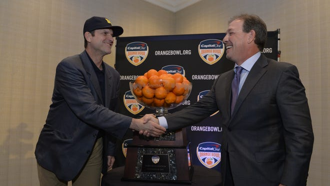 Florida State head coach Jimbo Fisher and Michigan head coach Jim Harbaugh shake hands during the coaches press conference before the Orange Bowl.