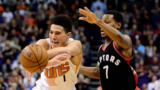 Suns guard Devin Booker (1) handles the basketball against Toronto Raptors guard Kyle Lowry (7) in the second half of Thursday night's game at Talking Stick Resort Arena.