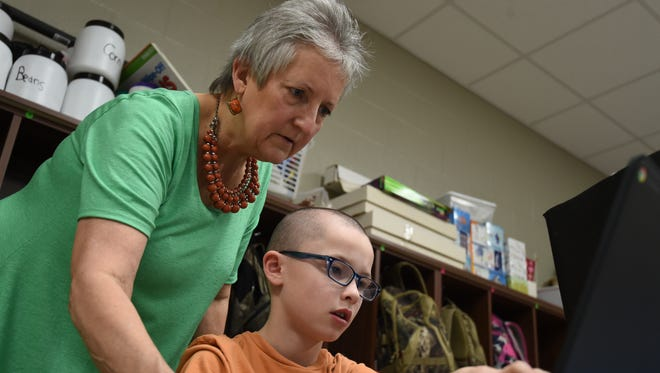 A Mountain Home teacher assists a student with spelling while working on a story during a reading class on Wednesday at Hackler Intermediate School. Arkansas created a reading campaign to help students read at grade level.