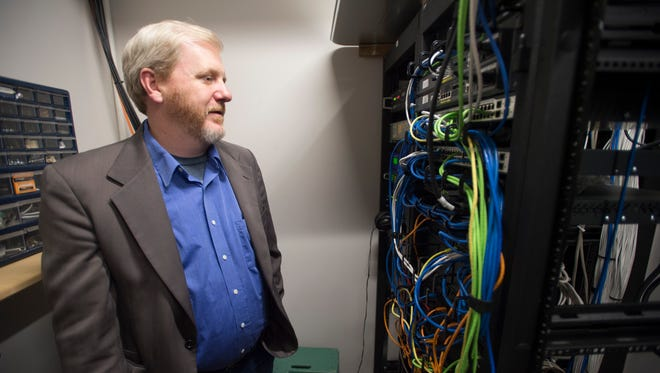 Executive Director Brian Hughes looks at the wiring that helps KRFC Public Radio run on Friday, March 10, 2017.