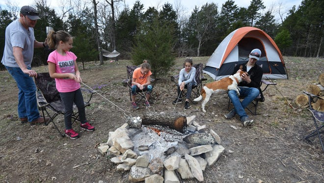 Lonnie Robinson, family physician for Regional Family Medicine, helps his daughter Mari Claire Robinson, 7, scoot closer to the fire as she and Chelsea Burns and Caroline Robinson, both 11, roast marshmallows on the family's property Friday while Stone Robinson pets the family dog, Ginger. Robinson recommends people to apply insect repellent to avoid picking up ticks.