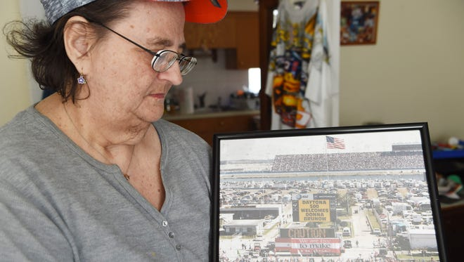 Donna Brunow, 66, holds a photo taken during one Daytona 500 in which she was welcomed on the Jumbotron by name, a gift from a friend. Brunow has been an avid collector of NASCAR memorabilia for 55 years.