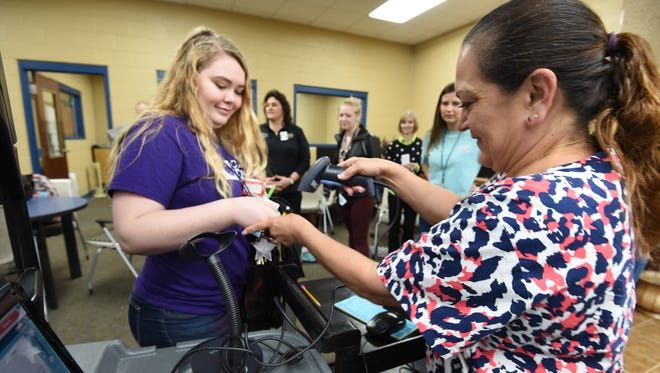 Cafeteria manager Alicia Barcelona scans Aubriana Chambers' card on Wednesday during the first day of the Bomber Grab and Go Breakfast program, which is allowing students to eat breakfast if they miss the school breakfast. Approximately 41 students came.