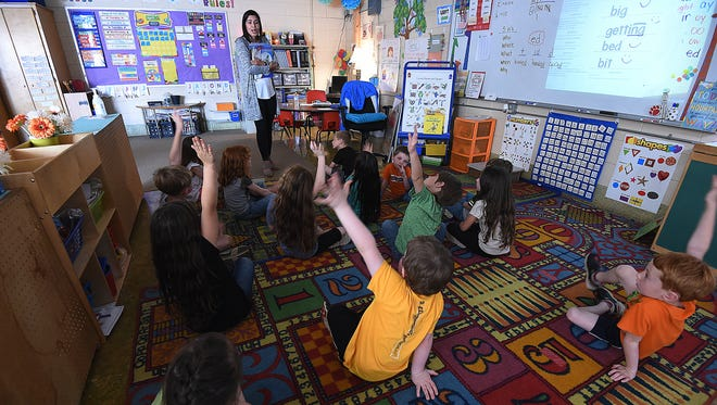 Students raise their hands to answer a vocabulary question in Alexis Thompson's Flippin kindergarten class. The district is working to align the curriculum to provide students with continuity moving from one grade to the next.