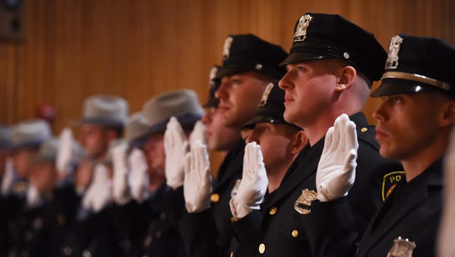 Police officers and deputy sheriffs take the oath of office during the graduation ceremony for the 20th Session of the Dutchess County Law Enforcement Academy Basic Course for Police Officers at Dutchess Community College.