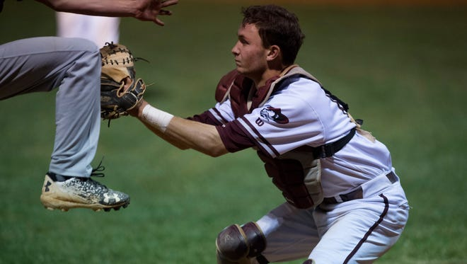 Henderson County catcher Jace Pinkston puts the tag on a Webster County runner as he tries to score by leaping past the catcher during the district game at Union County High School Monday night.