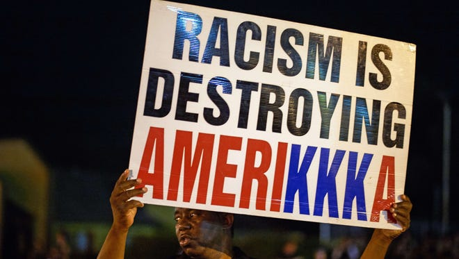 A man holds a sign during a protest on West Florissant Avenue in Ferguson, Mo., on Missouri on August 10, 2015.