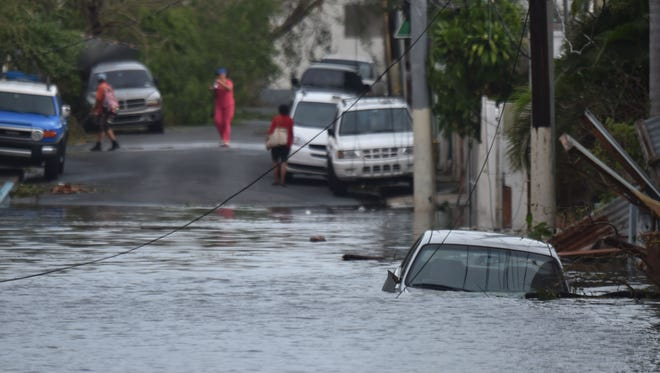 A car is stuck in a flooded street in in San Juan, Puerto Rico Sept. 21, 2017. 