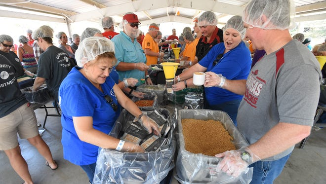 Volunteers pack meals at the 2017 Bridge Bash in Cotter. The Food Bank of North Central Arkansas fundraiser moves to the campus of Arkansas State University-Mountain Home on Saturday, but organizers still hope to collect enough donations to provide 500,000 meals and package another 100,000 on site.
