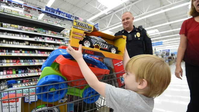 Sgt. Brian Corbett of the Mountain Home Police Department smiles Saturday morning as he watches three-year-old Robert Avant put a toy police car in a shopping cart during the annual Shop With a Cop event.