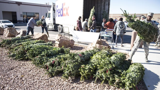 Volunteers unload and stack Christmas trees as a part of the Trees for Troops program at Holloman Air Force Base, N.M., Dec. 8, 2017. The Holloman Airman and Family Readiness Center received 150 free trees to hand out to Airmen and their families.