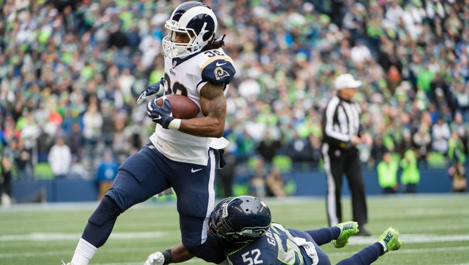 Los Angeles Rams running back Todd Gurley (30) picks up a first down during the first half as he is tackled by Seattle Seahawks outside linebacker Terence Garvin (52) at CenturyLink Field.