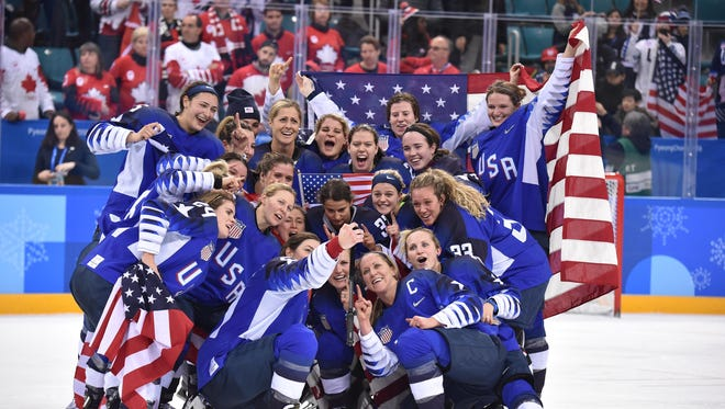 United States players celebrate after defeating Canada in the women's ice hockey gold medal game.