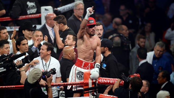 Ray Beltran celebrates his victory over Arash Usmanee (not pictured) after their lightweight title fight in 2014.