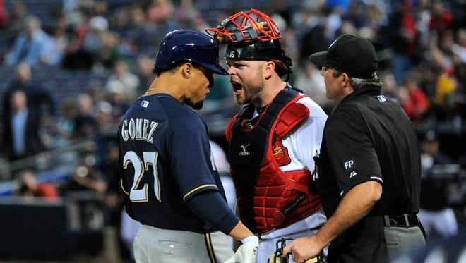 Brewers center fielder Carlos Gomez and Braves catcher Brian McCann exchange words.