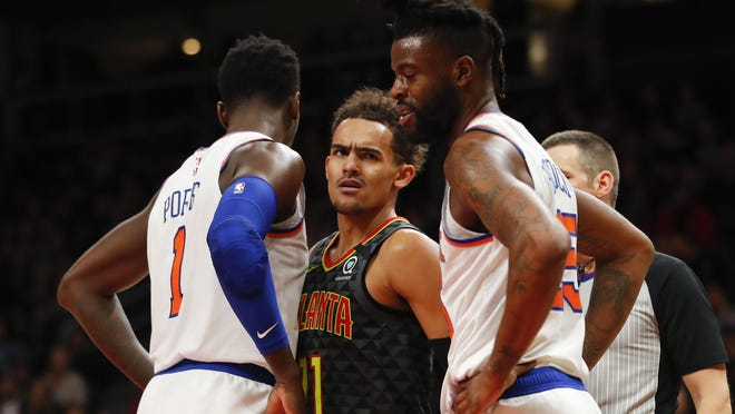 Hawks guard Trae Young (11) reacts between Knicks forward Bobby Portis (1) and guard Reggie Bullock (25) during a double-overtime game. The Knicks fell 140-135 [