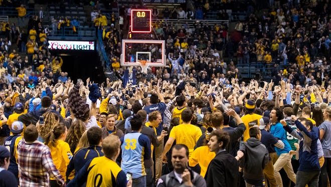 Marquette fans charge the court after the Golden Eagles stunned Villanova.