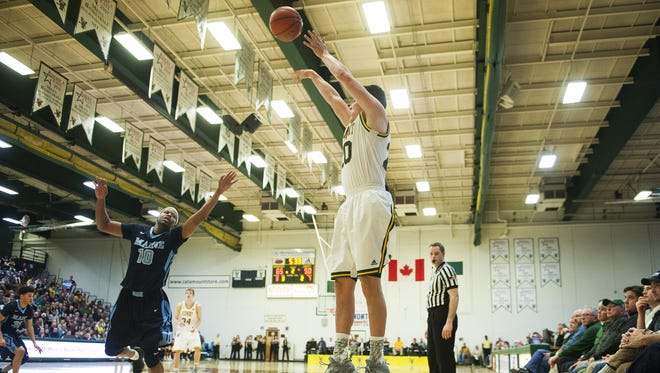 Vermont's Ernie Duncan (20) shoots a three pointer during the men's basketball game between the Maine Black Bears and the Vermont Catamounts at Patrick Gym on Wednesday night.