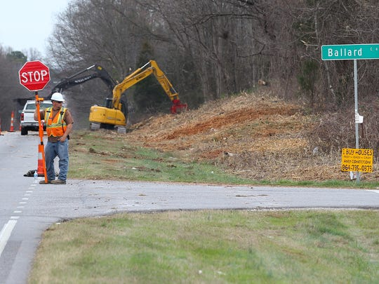 Danny McCormick of Batesburg holds a stop sign Tuesday in Anderson for traffic while other workers from the S.C. Department of Transportation clear brush and trees away from U.S. 29 North with a shin grinder.