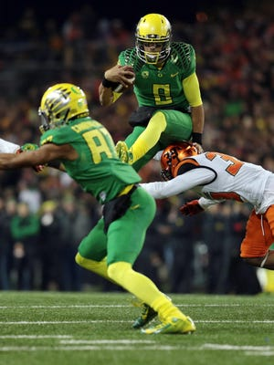 Oregon Ducks quarterback Marcus Mariota (8) jumps over Oregon State Beavers safety Justin Strong (39) in the first half at Reser Stadium.
