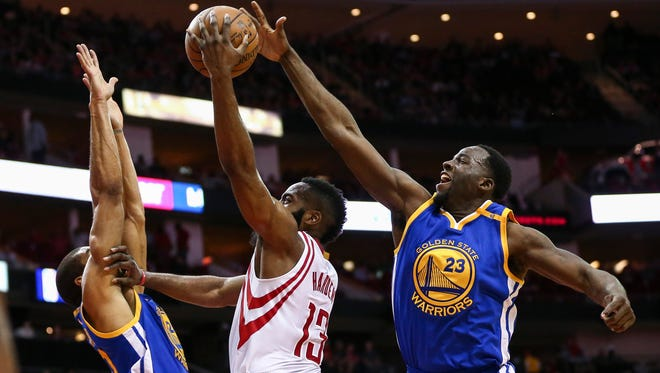 Golden State Warriors forward Draymond Green (23) attempts to block a shot by Houston Rockets guard James Harden (13) during the first quarter at Toyota Center.