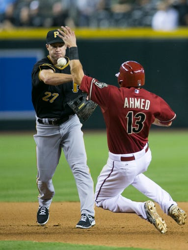 Diamondbacks' Nick Ahmed slides into second and has a the throw from Pirates' Jayson Nix come off his arm to prevent a doubleplay and score a walk-off win at Chase Field in Phoenix on Sunday, August 3, 2014.