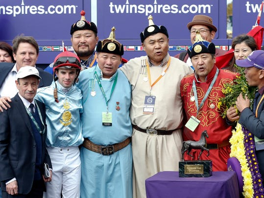 The owners of the horse Mongolian Saturday pose with jockey Florent Geroux, second from left in the front row, after Mongolian Saturday won the Breeders' Cup Turf Sprint horse race at Keeneland race track Saturday, Oct. 31, 2015, in Lexington, Ky. (AP Photo/Brynn Anderson)