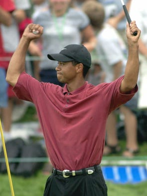 Tiger Woods celebrates after a birdie on the seventh playoff hole gave him the win over Jim Furyk in the NEC Invitational on Aug. 26, 2001 at Firestone Country Club in Akron, Ohio. Woods won the NEC Invitational for the third straight year.