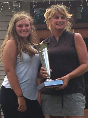Steph Urban, right, holds her championship trophy after winning her third consecutive EDWGA Match Play title. Urban beat Lydia Swan 1-up in the finals Sunday at Lake Shore Country Club. At left is Urban's daughter Taylor.