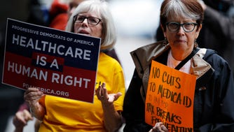 Jo Ann Waker-Ferrand, left, and Jan Miller, both of Denver, wave their placards during a protest against the Republican health bill that was recently unveiled in the U.S. Senate.