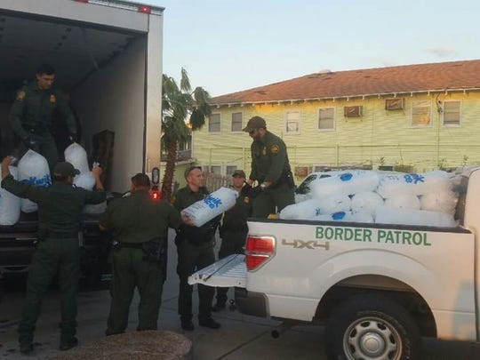 Rio Grande Valley Sector Mobile Response Team agents and the Brigada Internacional de Rescate Tlatelolco Azteca aid workers unload ice for residents in Rockport.