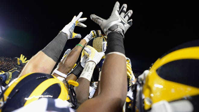The Michigan Wolverines hoist the Little Brown Jug after winning a game against the Minnesota Golden Gophers on Oct. 31, 2015, at TCF Bank Stadium in Minneapolis.