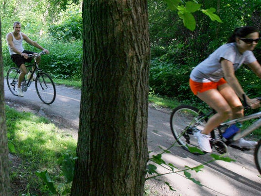 Cyclists ride through the Clive Greenbelt Trail