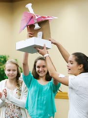 Shea Cunningham, 12, left, Thai West, 13, and Briana Hein, 14, present Babybrella, an umbrella for babies they helped create during the Girls Going Places Entrepreneurship Conference at FGCU on Wednesday. 140 local students learned about financial literacy and how to market products and start businesses.