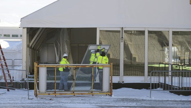Workers dismantle the Tundra Tailgate Zone tent at Lambeau Field. The tent will be replaced by a permanent structure.