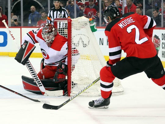 New Jersey Devils defenseman John Moore (2) plays the puck around the net of Carolina Hurricanes goaltender Scott Darling (33) during the second period at Prudential Center.