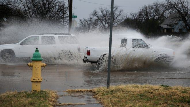 Vehicles spray up rainwater on Oakes Street on Tuesday. San Angelo has received more than 1 inch of moisture so far this month.